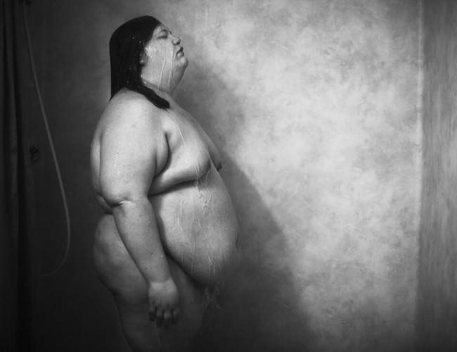 Schwarzweißfoto einer duschenden Frau.