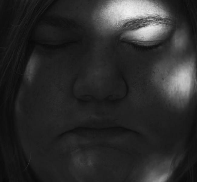 Schwarzweißportrait einer Frau mit geschlossenen Augen.