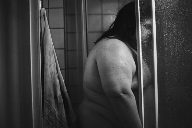 Schwarzweißbild einer nackten Frau in einer Dusche.