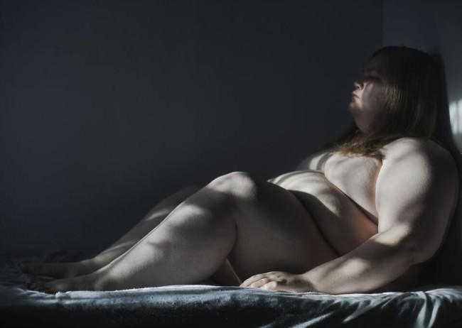 Eine nackte Frau sitzt auf einem Bett.