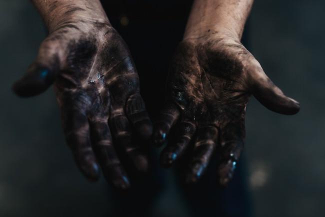 Hände voll von schwarzem Öl.