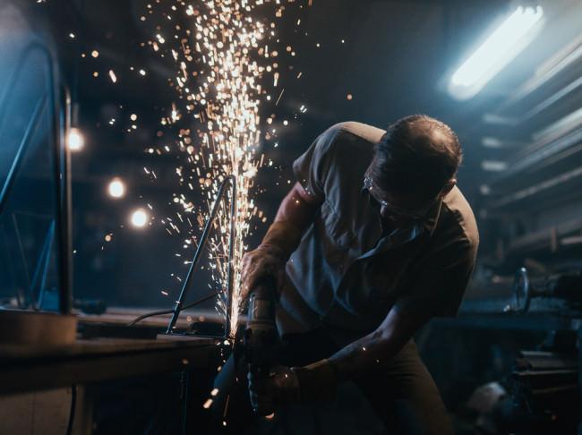 Ein Metallarbeiter bei der Arbeit. Funken sprühen.