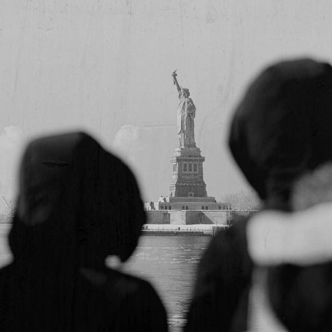Blick auf die Freiheitsstatue, zwei Köpfe im Vordergrund