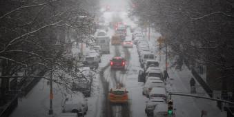 Autoverkehr auf einer verschneiten Straße in New York.