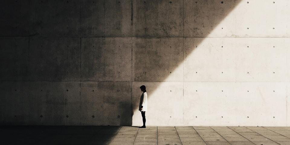 Eine Frau vor einer hohen Betonwand, halb im Licht, halb im Schatten stehend.