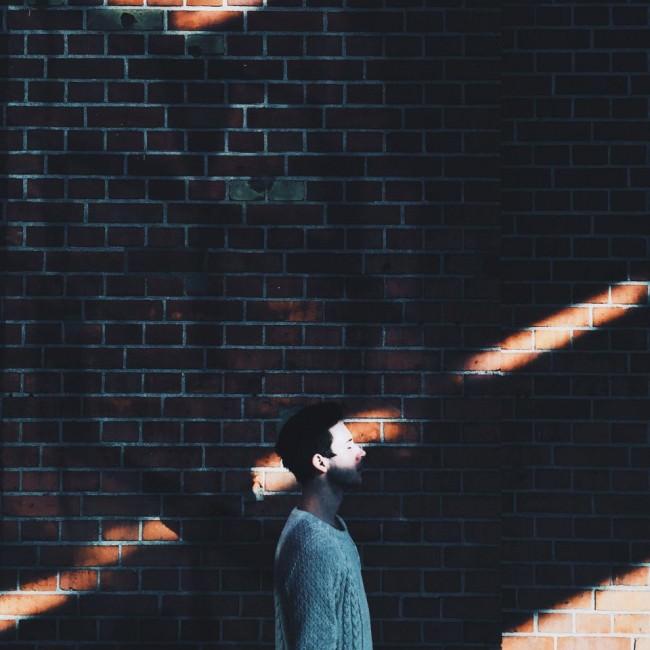 Ein Mann steht vor einer Backsteinmauer und wird von Lichtstreifen gestreift.