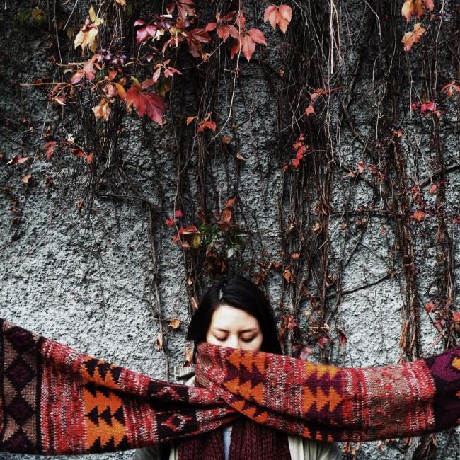 Eine Frau vor einer Wand mit roten Weinblättern und einem gemusterten Schal in den gleichen Farben.