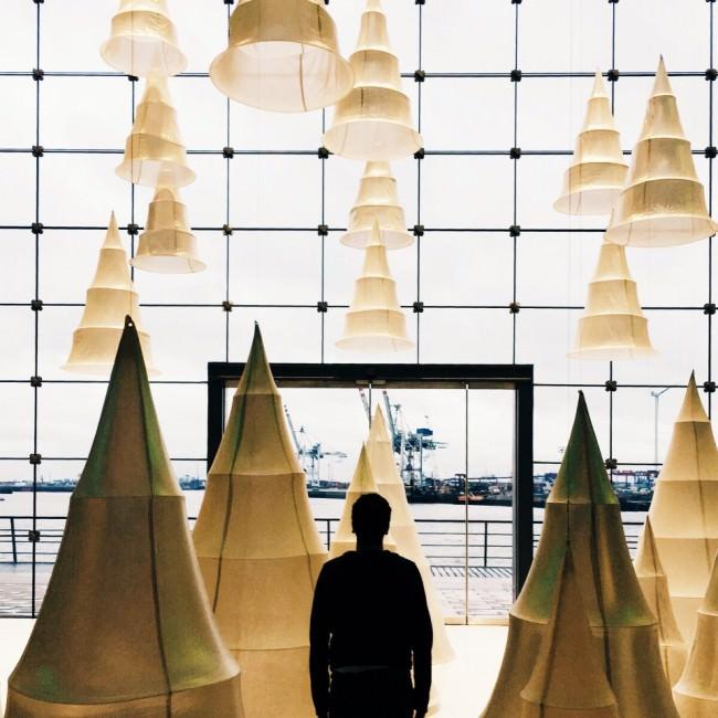 Ein Mann in einem großen Raum vor einer deckenhohen Fensterfront, umgeben von im Raum schwebenden Lampenobjekten.