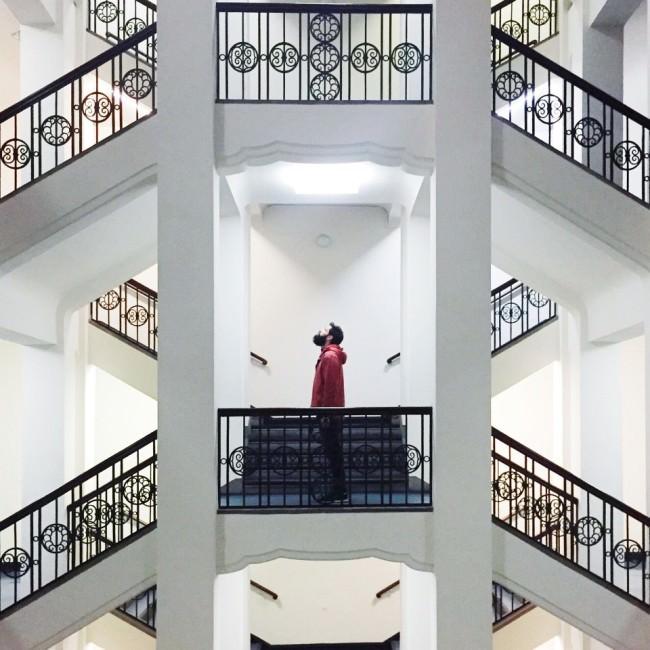 Ein Mann in einem hellen, symmetrischen Treppenhaus mit schmiedeeisernen Geländern.