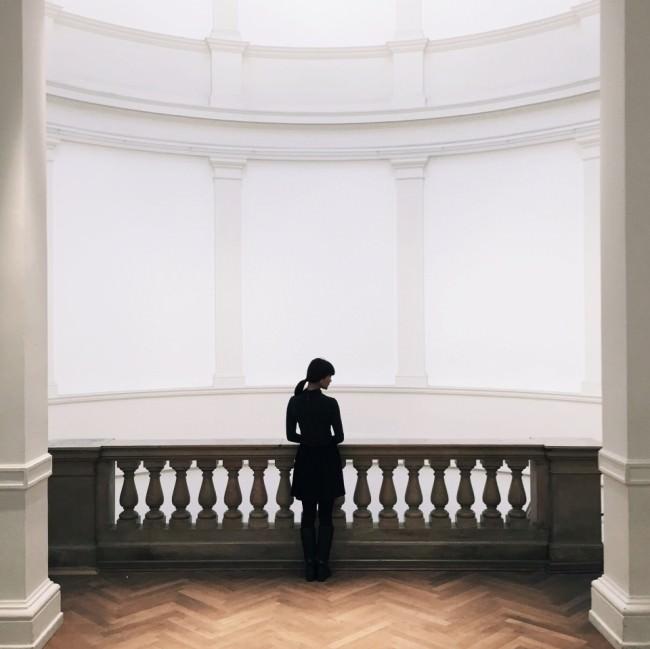 Eine Frau steht an einer Ballustrade, hinter der sich ein großer, weißer Raum öffnet.