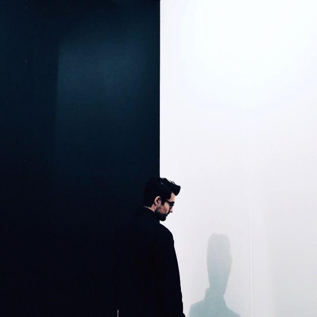 Ein Mann vor einer schwarz-weiß-geteilten Wand.