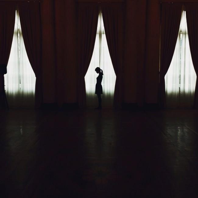 Die Silhouette einer Frau, im Dunkeln durch Fenster mit Vorhängen sichtbar.