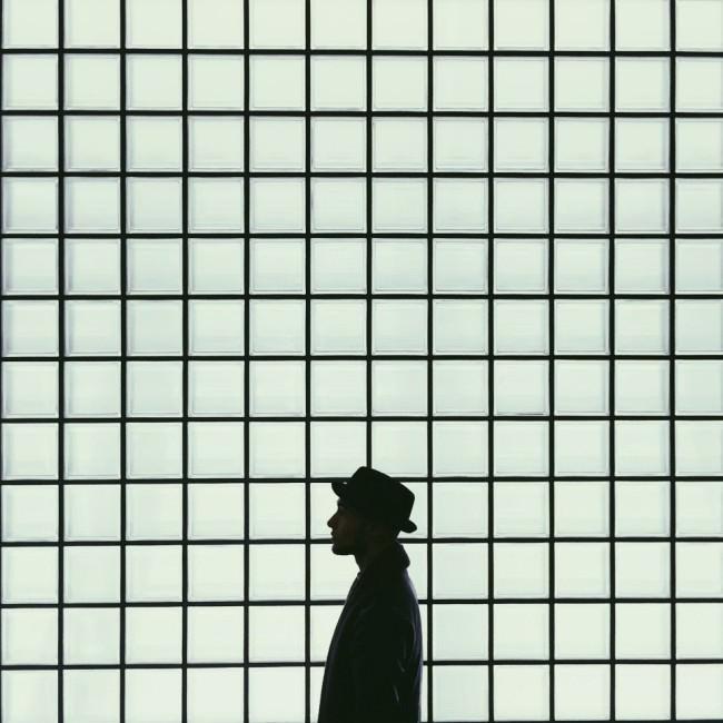 Ein Mann mit Hut vor einer Wand aus Quadraten.