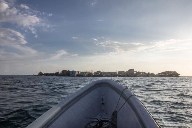 Blick von einem kleinen Boot aus auf eine Stadt am Horizont des Meeres.