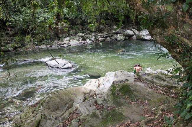 Zwei Menschen sitzen an einem Fluss im Urwald.