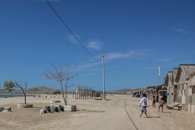 Kinder spielen auf einer Straße in der Wüste.