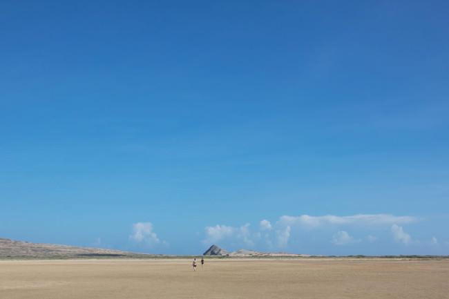 Eine weite Sandfläche. In der Ferne sieht man zwei Menschen.