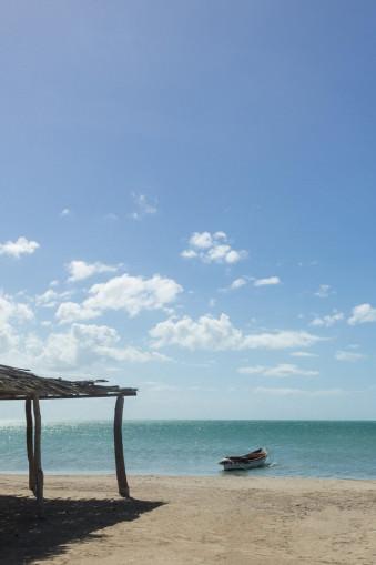 Kleine Hütte mit Boot am Strand.