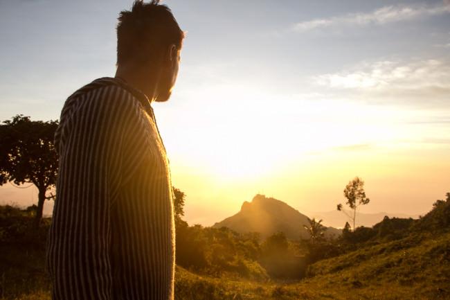 Ein Mann betrachtet den Sonnenuntergang und wird in goldenes Licht getaucht.