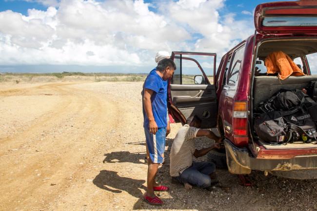 Männer an einem kaputten Auto.