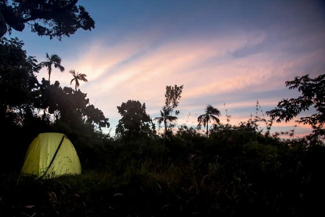 Ein gelbes Zelt in der Wildnis. Am Himmel sieht man die letzten roten Lichter der Abendsonne.