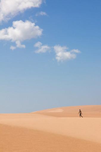 Ein Mensch läuft durch Sanddünen. über ihm der Blaue Himmel mit einzelnen Wolken.