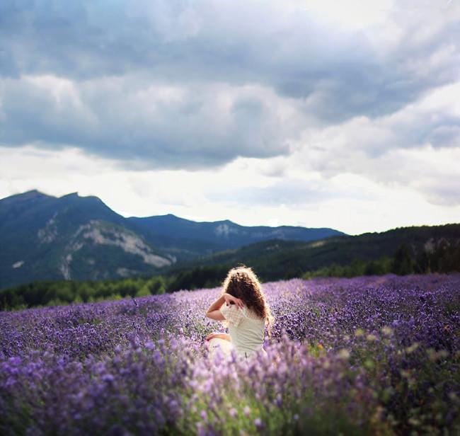 Eine Frau sitzt zwischen Lavendel