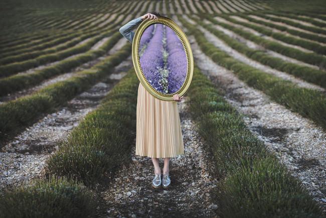 Eine Frau mir Spiegel im Lavendelfeld