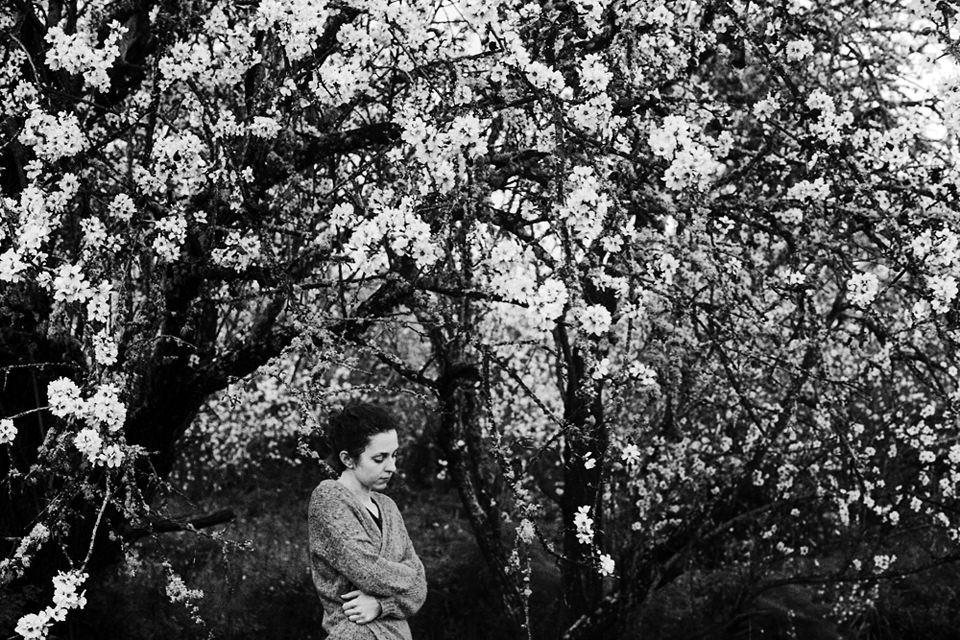 Eine Frau zwischen blühenden Bäumen