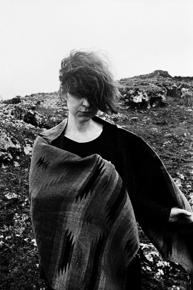 Eine Frau mit Decke und Wind in den Haaren.