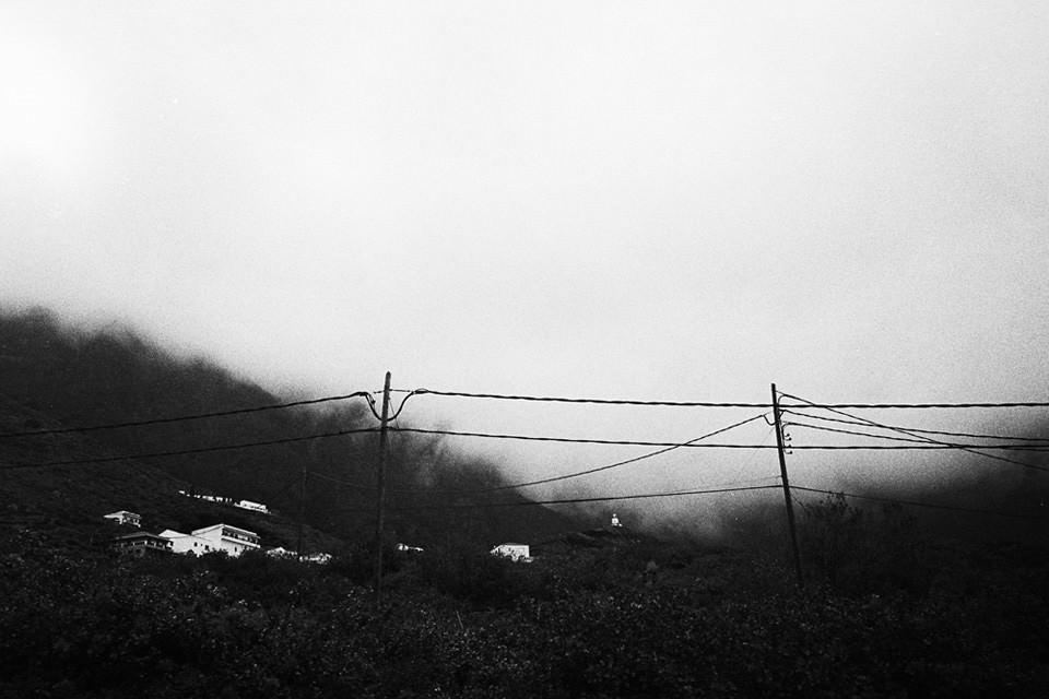 Ein Zaun der im Hintergrund den Blick auf ein Dorf freigibt.