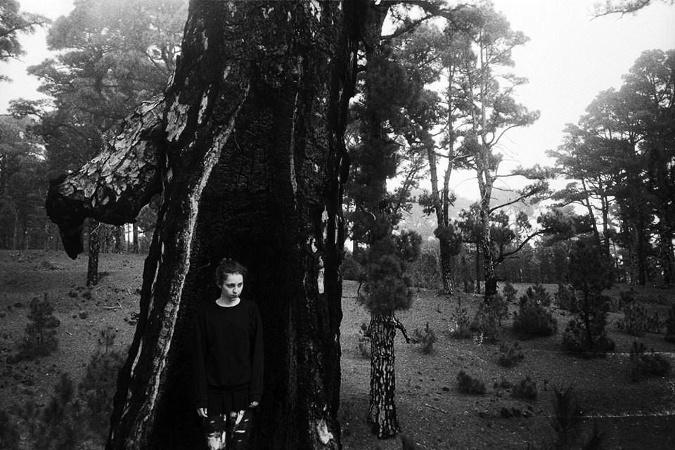 Eine Frau steht in einer Baumhöhle.