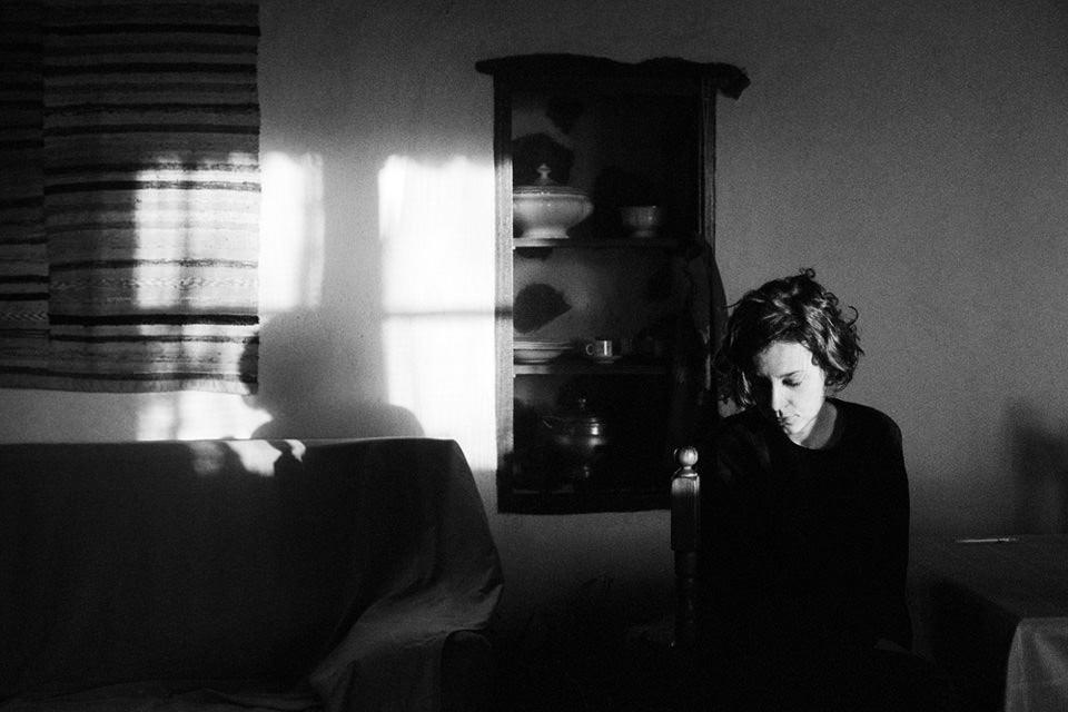 Eine Frau in einem Zimmer. Licht fällt durch die Fensterscheiben auf die Wand.