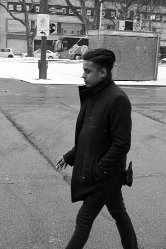 Ein junger Mann geht rauchend über eine Straße