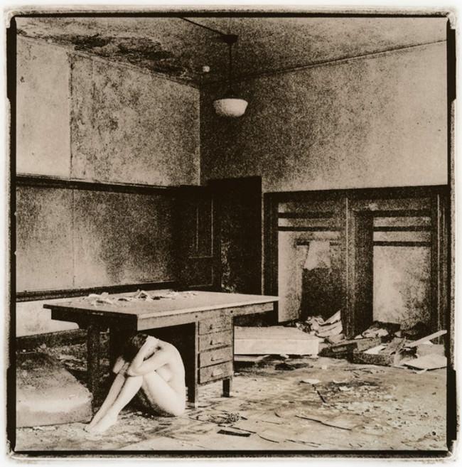 Eine Frau sitzt unter einem Tisch in einem verlassenen Klassenraum.