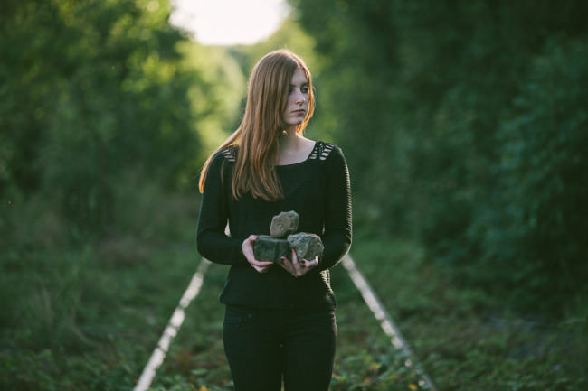 Frau mit Steinen auf Bahngleisen