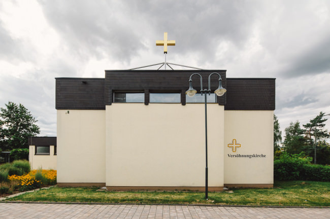 Flachdach-Kirche mit bewölktem Himmel