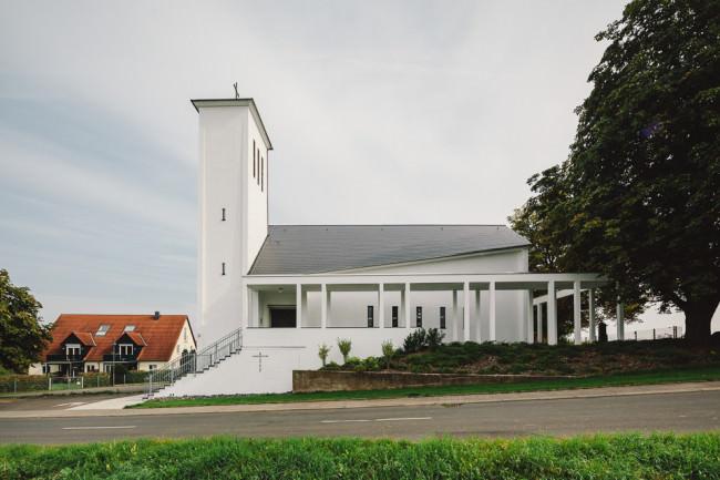 Weißes Kirchengebäude mit Arkaden seitlich
