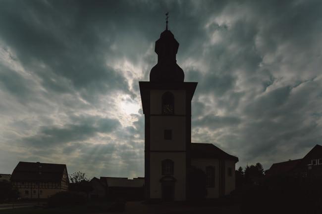 Silouette einer Kirche vor bewölktem Sonnenhimmel
