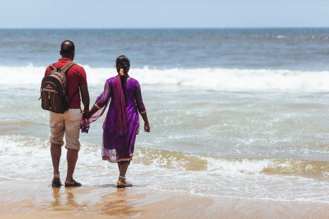 Indisches Pärchen am Strand mit Wellen