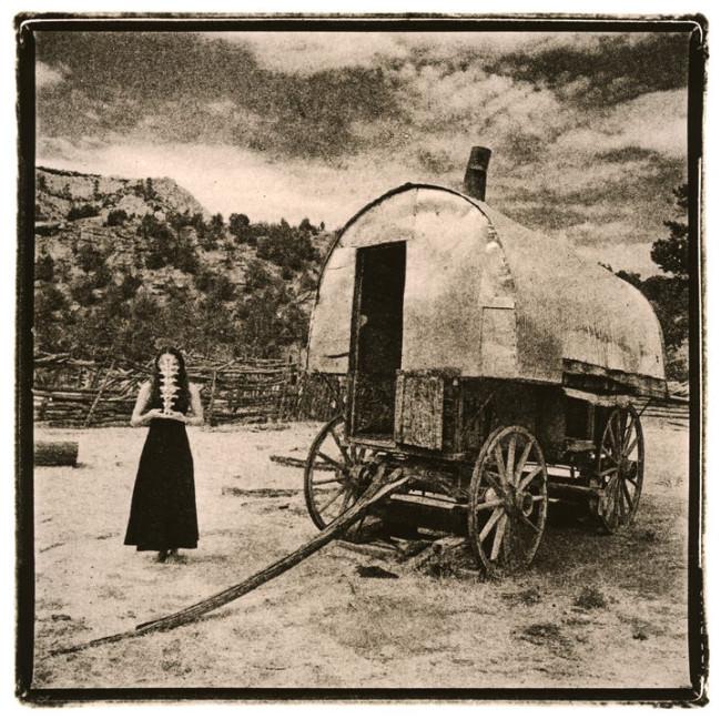 Ein alter Planwagen und eine Frau davor.
