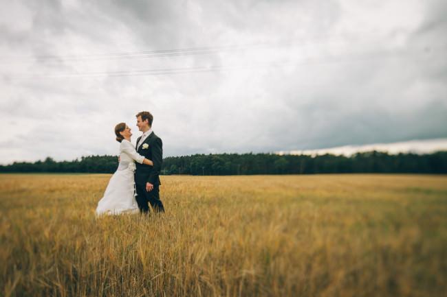 Hochzeitspaar im Kornfeld unter bewölkten Himmel
