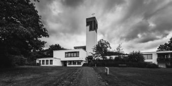 Moderne Kirche vor düsterer Wolkenfront