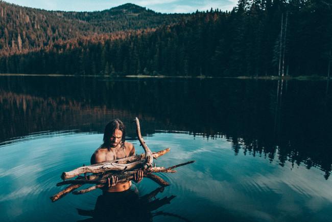 Mann mit Holzstapel in See am Waldrand
