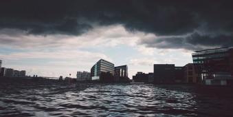 Eine Stadt am Wasser, über der dunkle Wolken hängen.