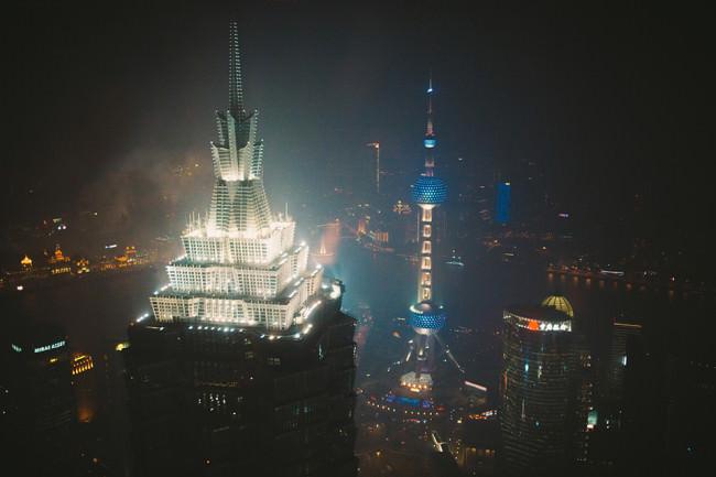 Hell erleuchtete futuristische Hochhäuser in einer asiatischen Großstadt.