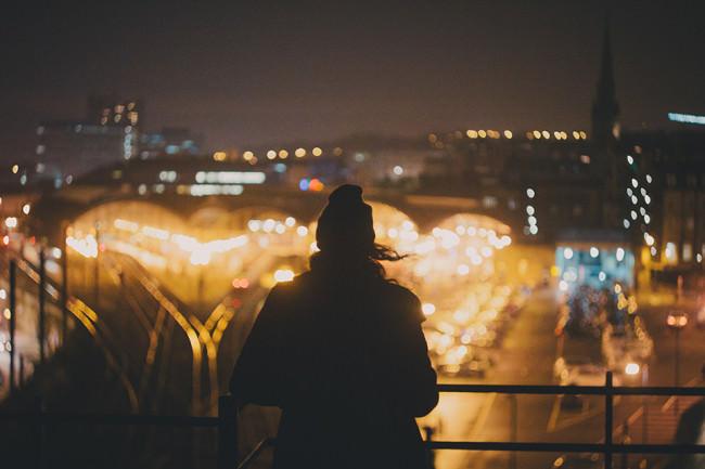 Eine Person steht auf einer Brücke und schaut auf eine erleuchtete Stadt herunter.
