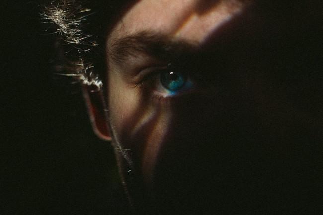Nahes Portrait eines Mannes, dessen Gesicht halb von Dunkelheit verdeckt ist.