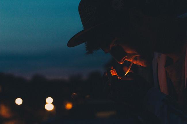 Ein Mann mit Hut zündet sich im Dunkeln eine Zigarette an.