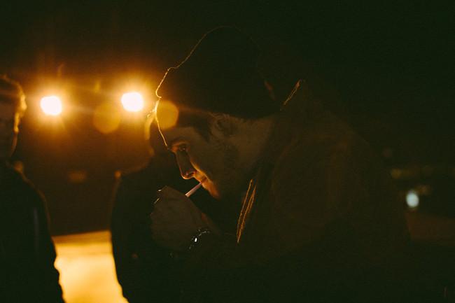 Ein Mann mit Mütze zündet sich im Dunkeln eine Zigarette an.